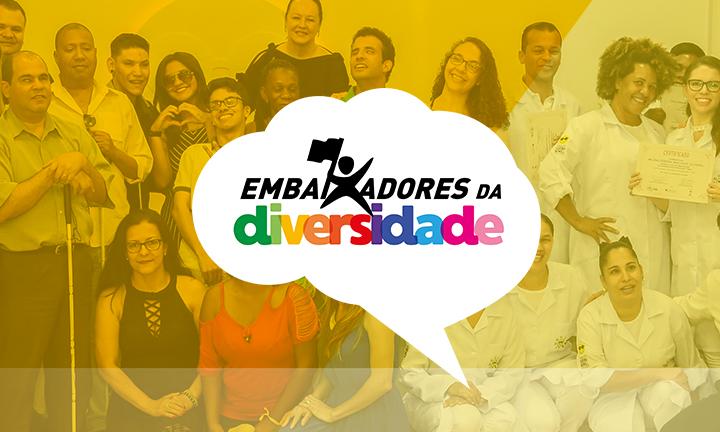 """Descrição da imagem: foto em tons amarelados de um grupo de 30 pessoas perfiladas, olhando pra frente e sorrindo. Algumas usam bengalas. No meio da imagem há um balão de pensamento com o título """"Embaixadores da Diversidade"""""""