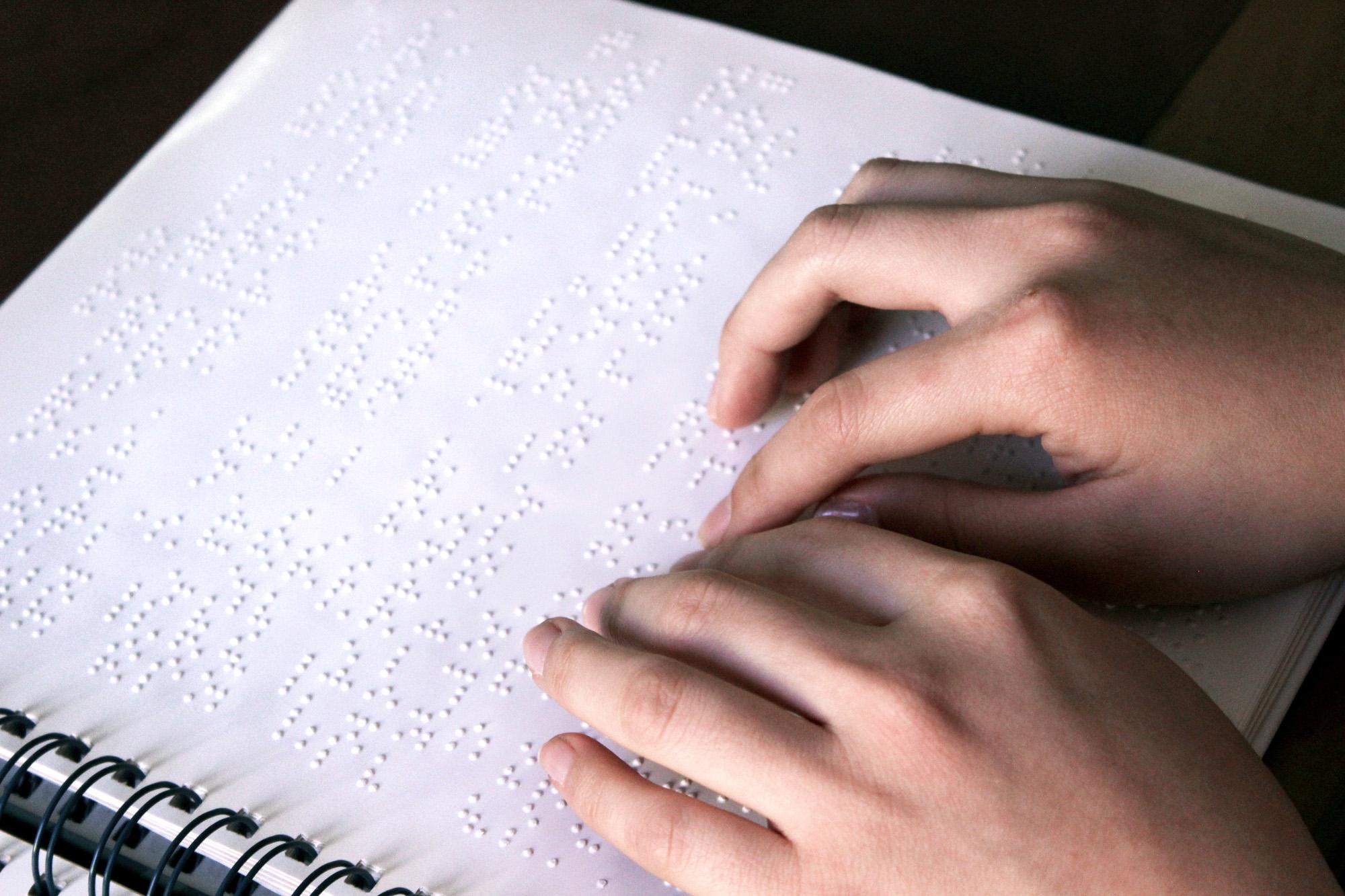 Descrição da imagem: foto de duas mãos sobre papel com texto em braille