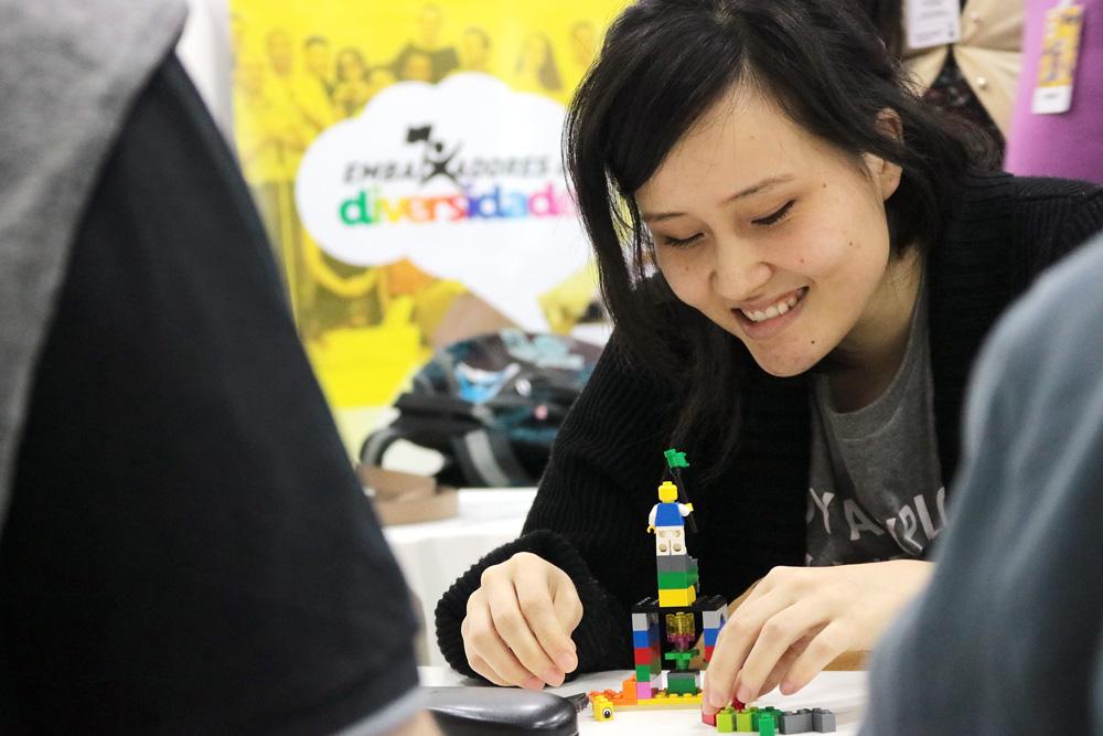 """Descrição da imagem: foto de moça de traços orientais manuseando peças de Lego e sorrindo. Ao fundo há um banner do projeto """"Embaixadores da Diversidade"""""""