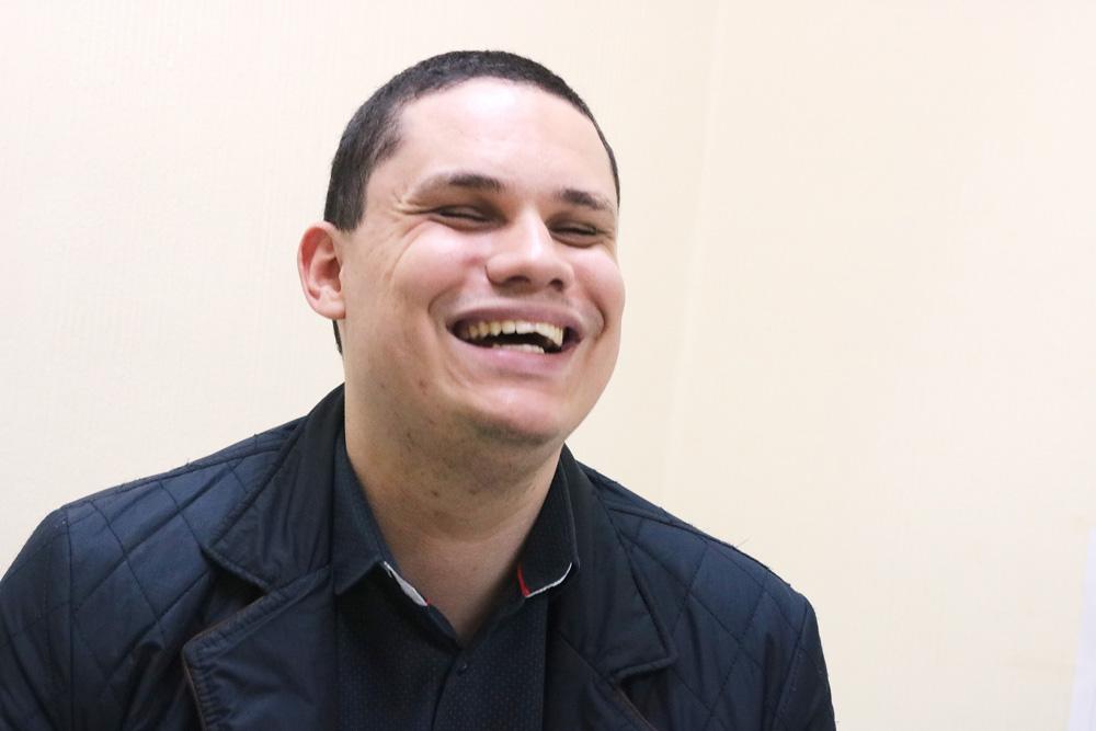 Descrição de imagem: Foto de Caio olhando para frente e sorrindo.