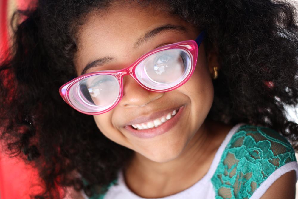 Descrição da imagem: foto de uma garotinha sorridente de óculos cor-de-rosa. Ela é negra, tem cabelos cacheados e usa camiseta branca com mangas verdes.