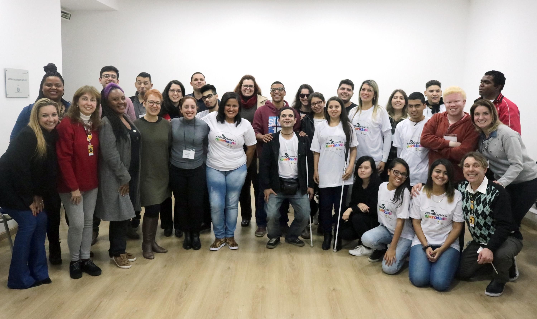 Descrição da imagem: Foto de um grupo de 30 pessoas olhando para a foto e sorrindo. Elas estão dispostas lado a lado e algumas pessoas estão abaixadas na frente.