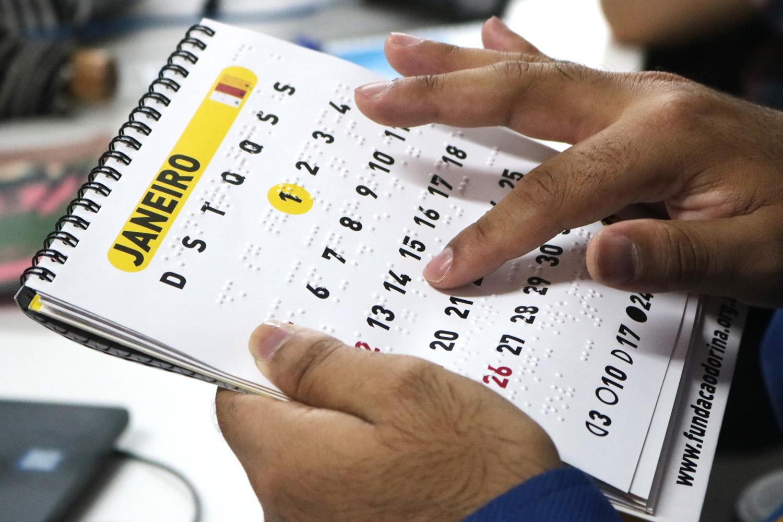 Descrição de imagem: Duas mãos segurando e tocando um calendário em braille no mês de janeiro.