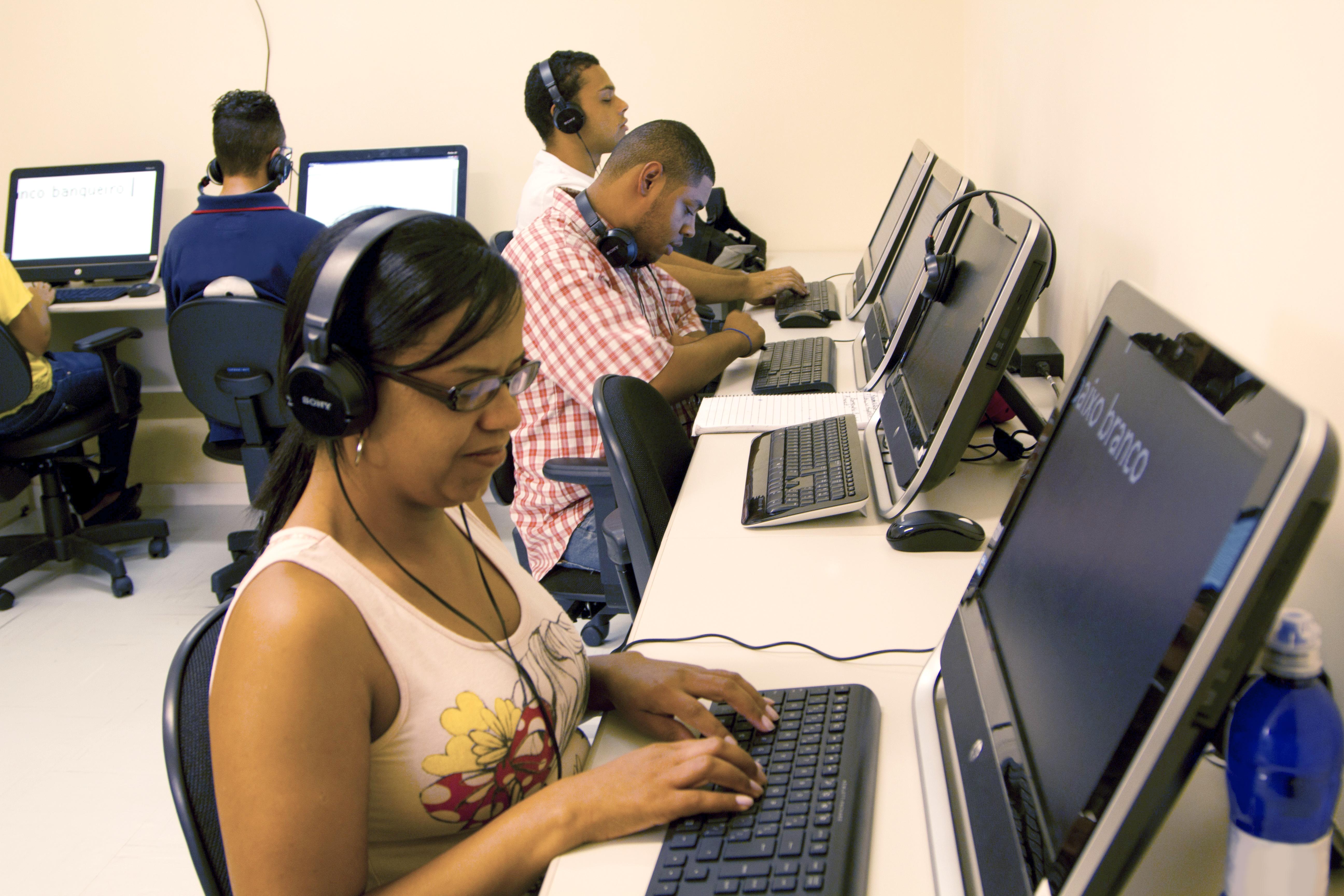 Imagem de cinco alunos da Fundação na sala de informática. Três deles, dois rapazes e uma moça, estão sentados de perfil, voltados para o lado direito. Eles utilizam headfones e estão com as mãos sob os teclados dos computadores. Outro rapaz está sentado de costas, na parede do fundo da imagem, também com headfone. Ao lado dele, está outro aluno, porém só aparece o seu braço na imagem.