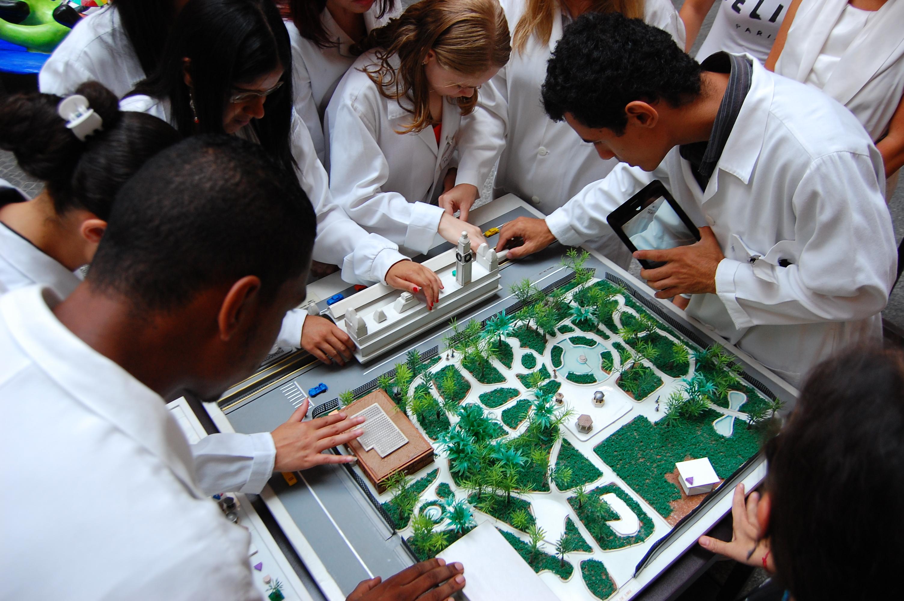 Imagem vista do alto de alunos da Fundação Dorina tateando uma maquete tátil do jardim da Pinacoteca. Eles estão de jalecos brancos, ao redor da maquete.
