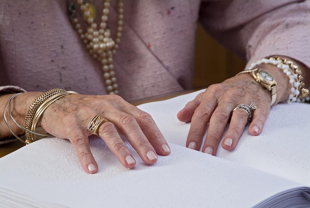 Foto das mãos de Dona Dorina sobre um livro braille. Suas mãos estão adereçadas com anéis, diversas pulseiras e um relógio. Ela veste um casaco rosa, com colar de pérolas.