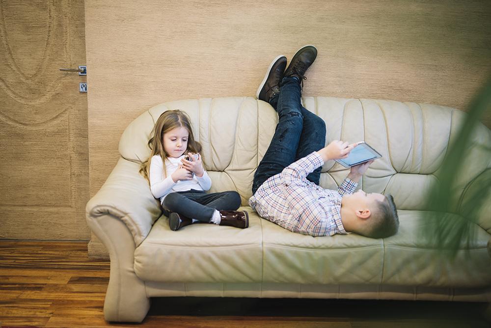 Imagem de duas crianças sentadas em um sofá. À esquerda está uma menina sentada com as pernas cruzadas, utilizando um celular perto dos olhos. Ao lado direito, está um menino sentado com as pernas para cima, de modo que suas costas e sua cabeça estão encostados no assento do sofá. Ele está utilizando um tablet.