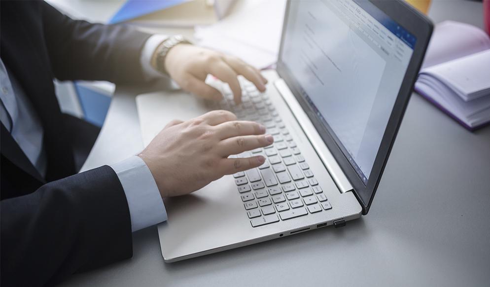 Descrição da imagem: foto de duas mãos sobre um notebook aberto sobre uma mesa.