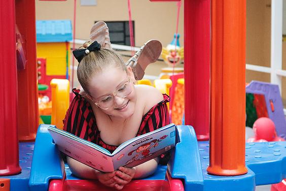 Descrição da Imagem: foto de Isabella, criança atendida pela Fundação, no parquinho. Ela está deitada, com as pernas cruzadas para o alto e com um livro infantil aberto à sua frente. Ela sorri ao ler o livro.