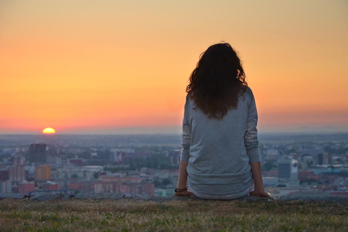 Descrição da imagem: foto de mulher de costas sentada numa mureta observando o por do sol. Ela está em um ponto alto de uma cidade, com uma vista repleta de casas e prédios lá em baixo.