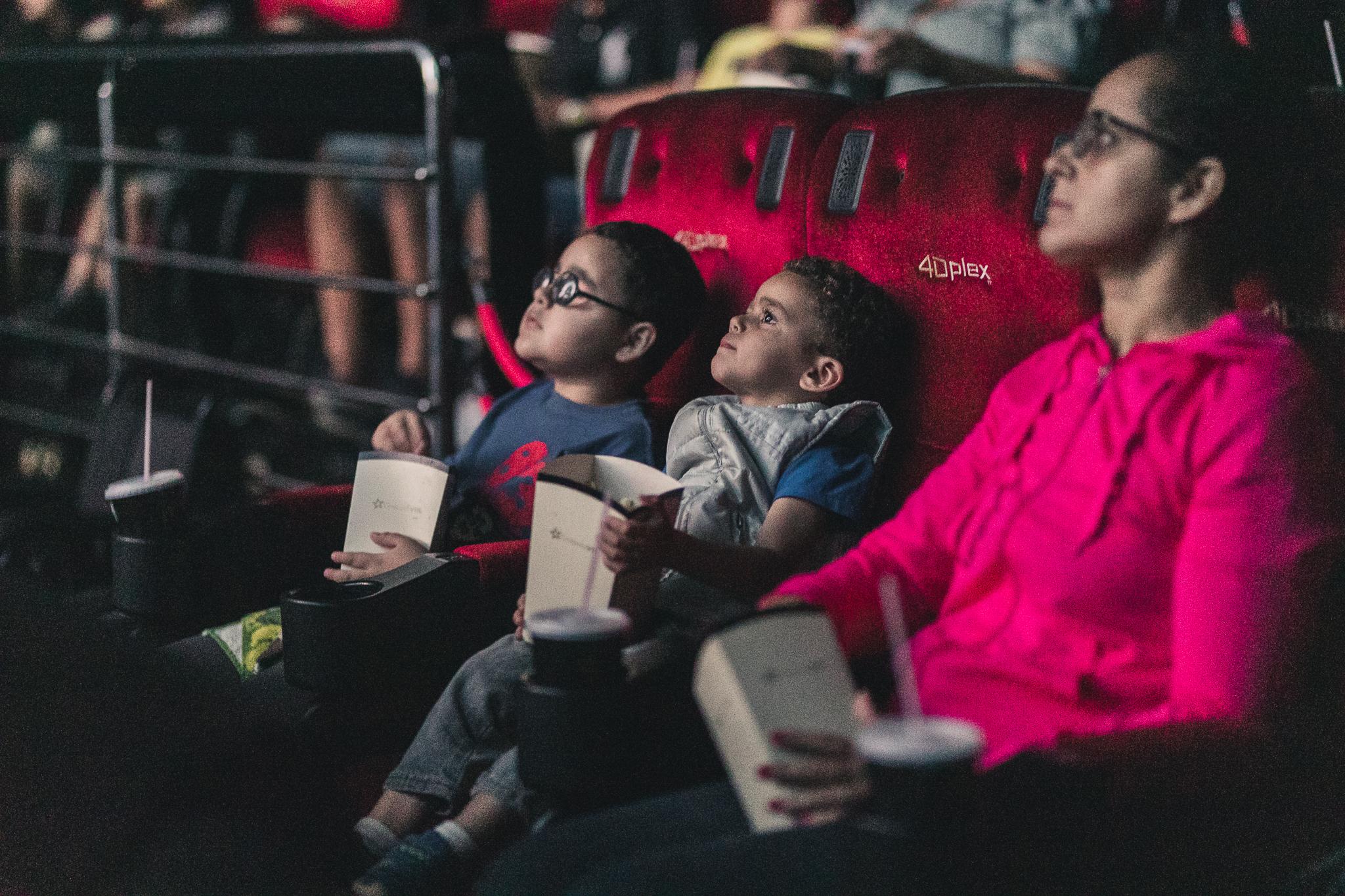 Imagem de uma sessão de cinema inclusivo promovido pelo Telecine. Em destaque, há dois meninos e uma mulher sentados em poltronas de cinema. Eles olham para frente e estão segurando embalagens de pipoca nas mãos.