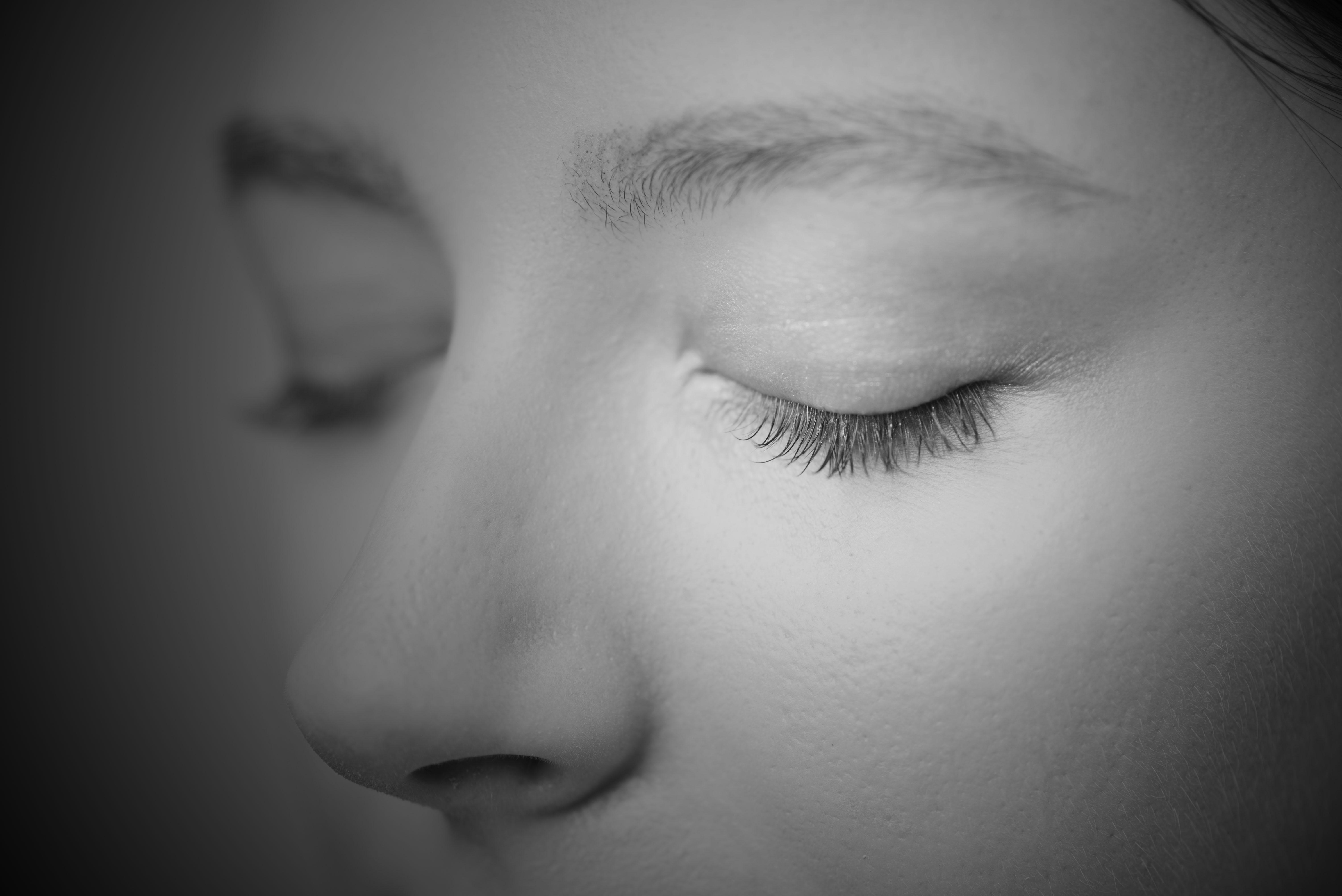Descrição da imagem:foto em preto e branco do rosto de uma mulher de olhos fechados.