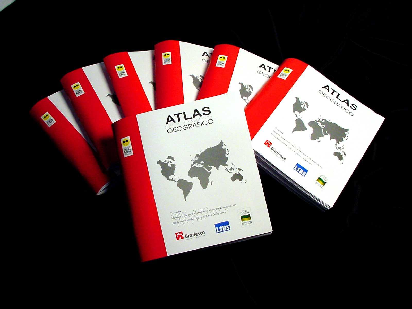 """Imagem de fundo preto. No centro há diversos livros braille didáticos. Eles tem capa branca, com a lombada vermelha. No topo da capa está escrito """"ATLAS"""" e abaixo está desenhado o mapa mundi."""