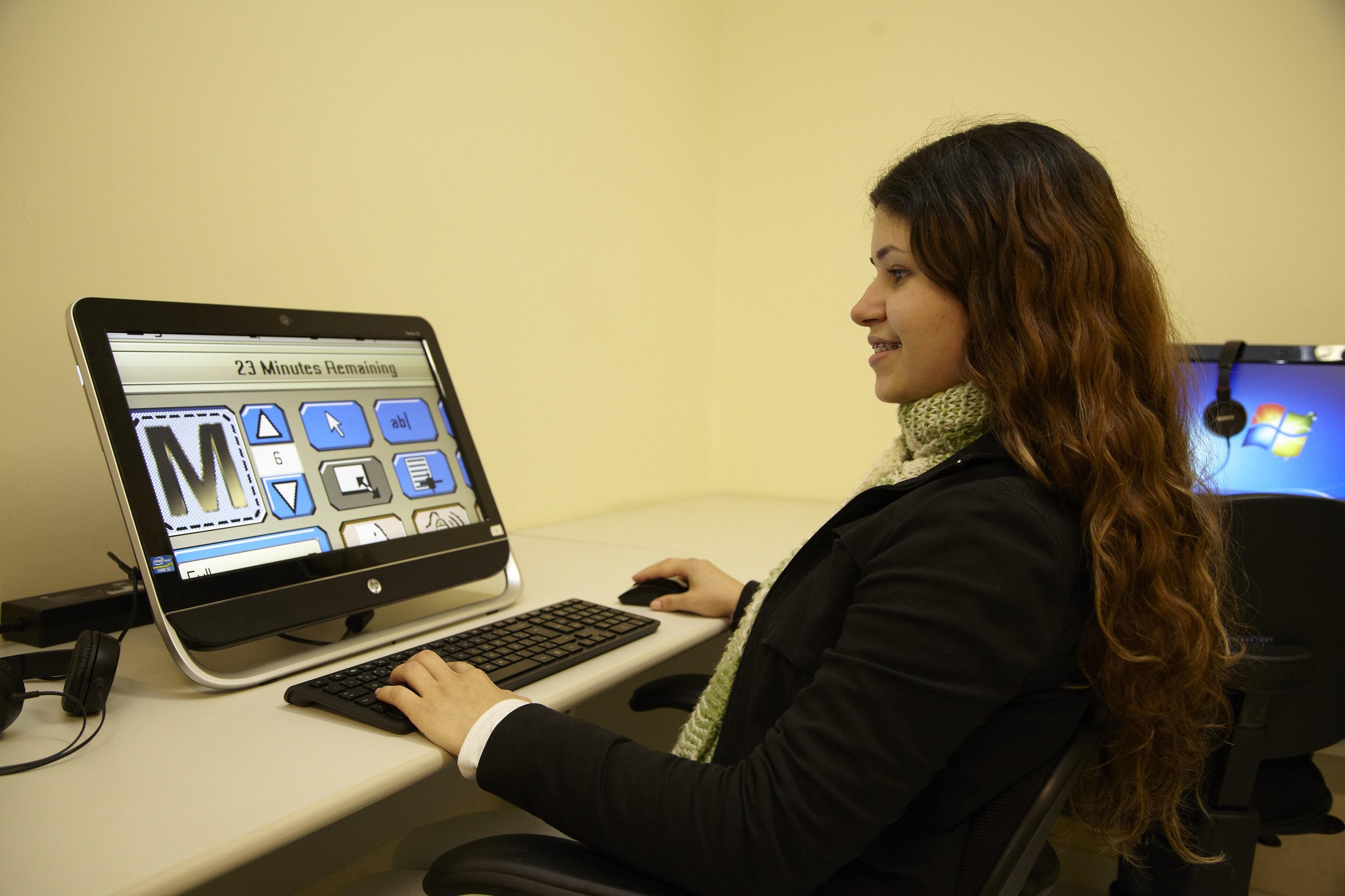 Descrição da imagem: foto de mulher sorridente de perfil usando computador.
