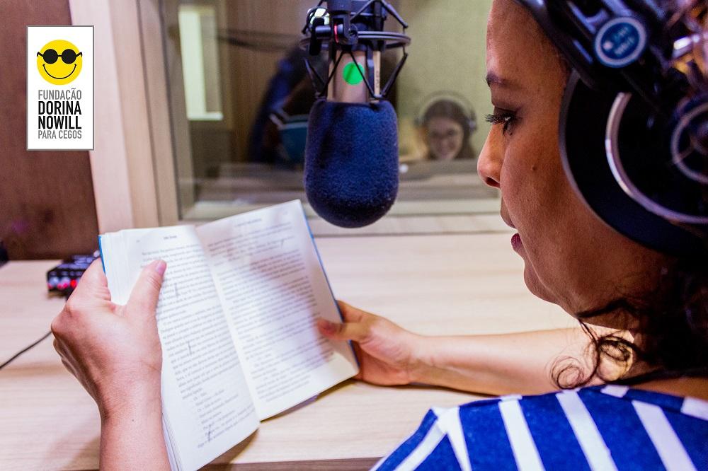 Descrição da imagem: foto de mulher em meio perfil segurando um livro aberto sobre mesa. Ela usa fones de ouvido e tem um microfone de estúdio à sua frente. Ao fundo, por detrás de uma vidraça, há uma moça sorridente também usando fones de ouvido. No canto superior esquerdo há o logotipo da Fundação Dorina.